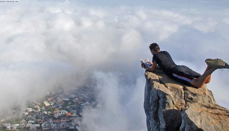 Student is reading lying on a high mountain among the clouds and below we see a valley.
