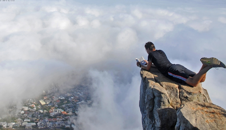A student on exchange is lying down and reading on a mountain top, among the clouds, overlooking a village.